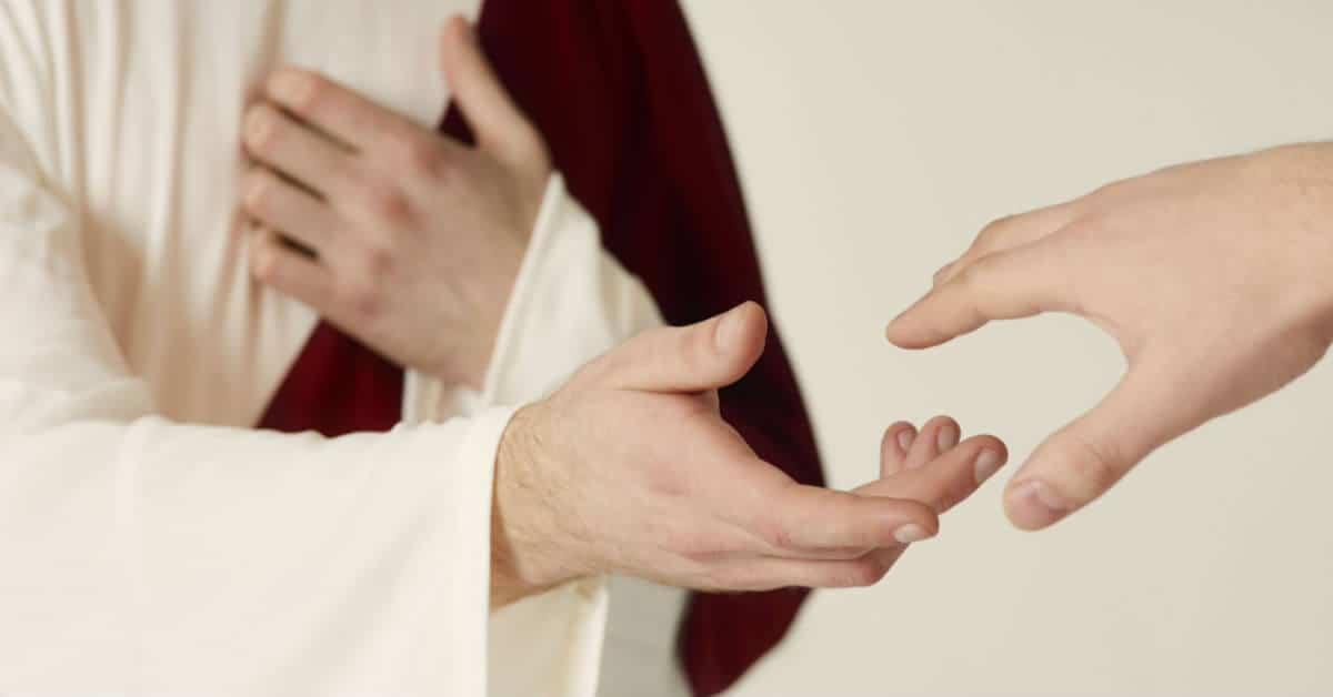 Image of a person representing Jesus holding out his hand to a person who is holding out his hand to Jesus.