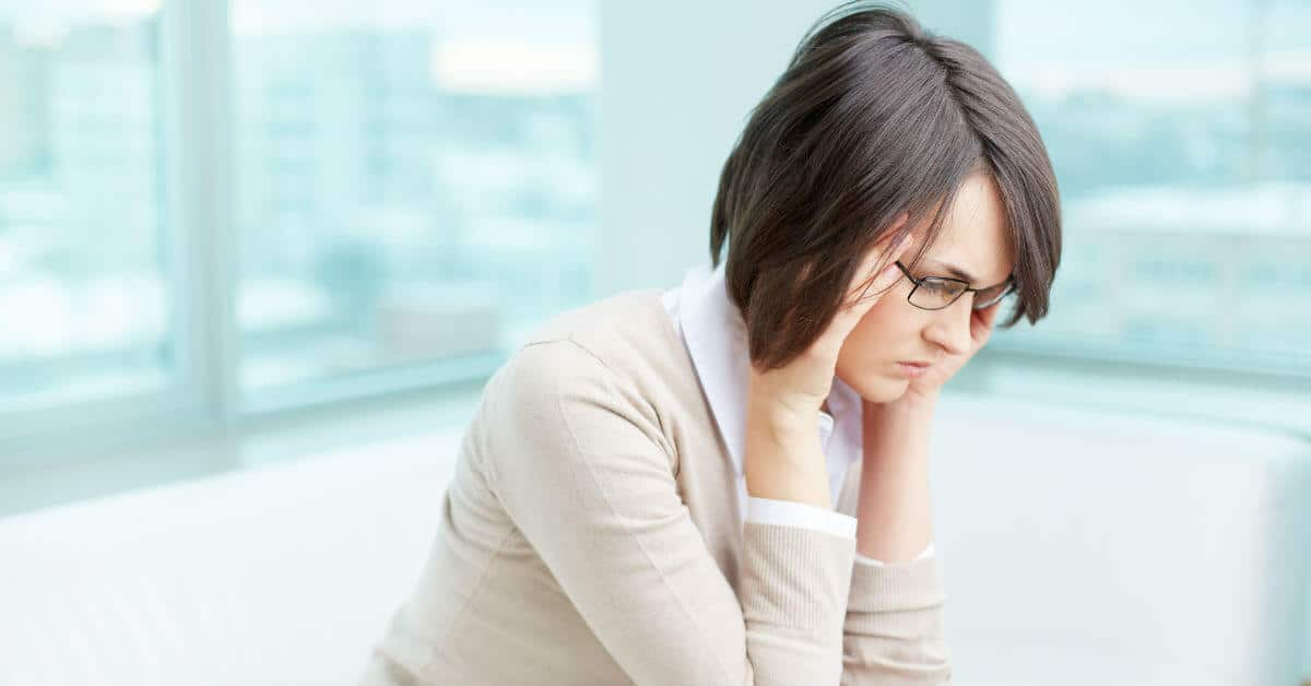 Image of a woman looking down, holding her face with her elbows on her knees.