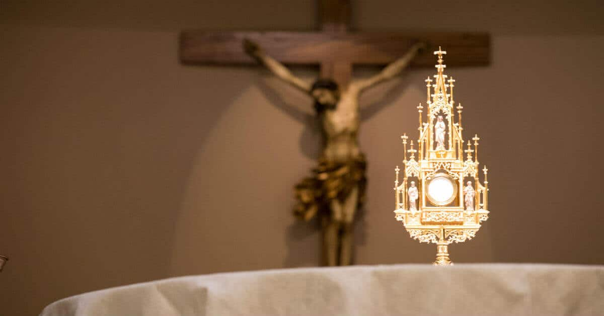 Image of Jesus crucified and a golden monstrance with a host.