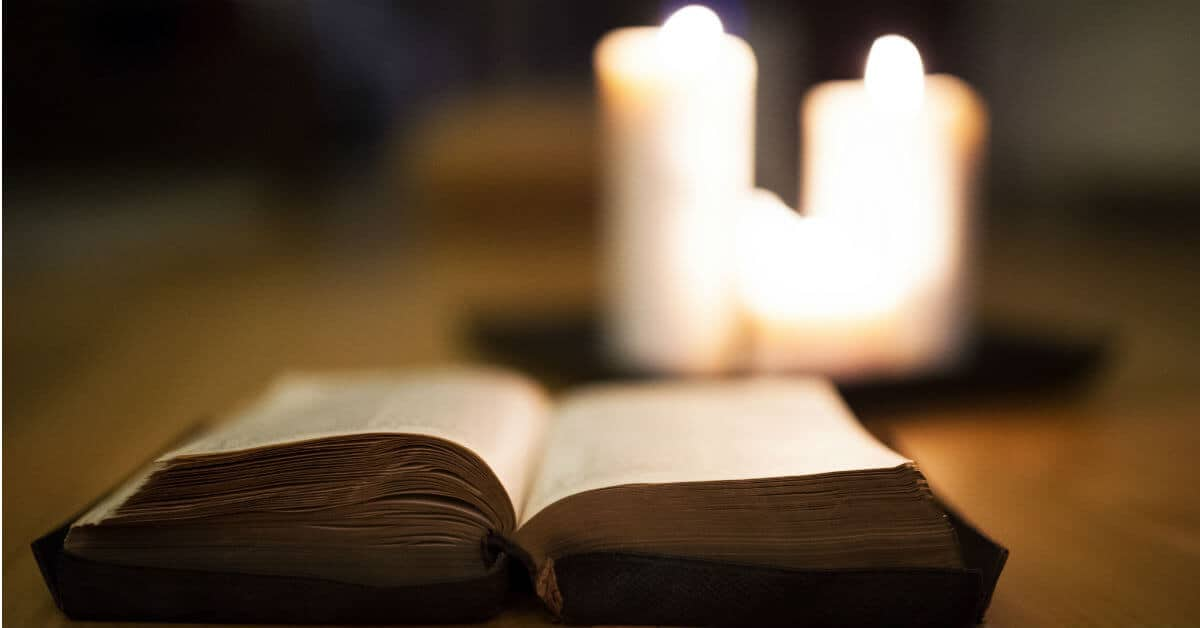 Image of an open Bible with three white candles lit behind it.