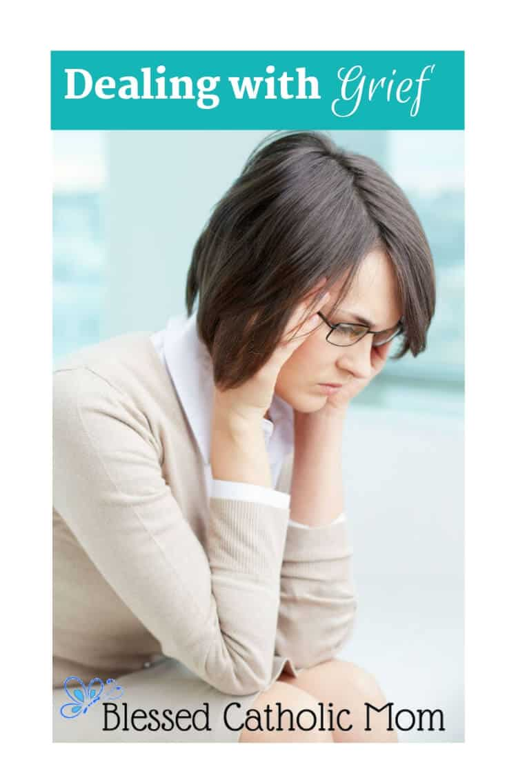 Image of a woman looking down, holding her head with her elbows on her knees.