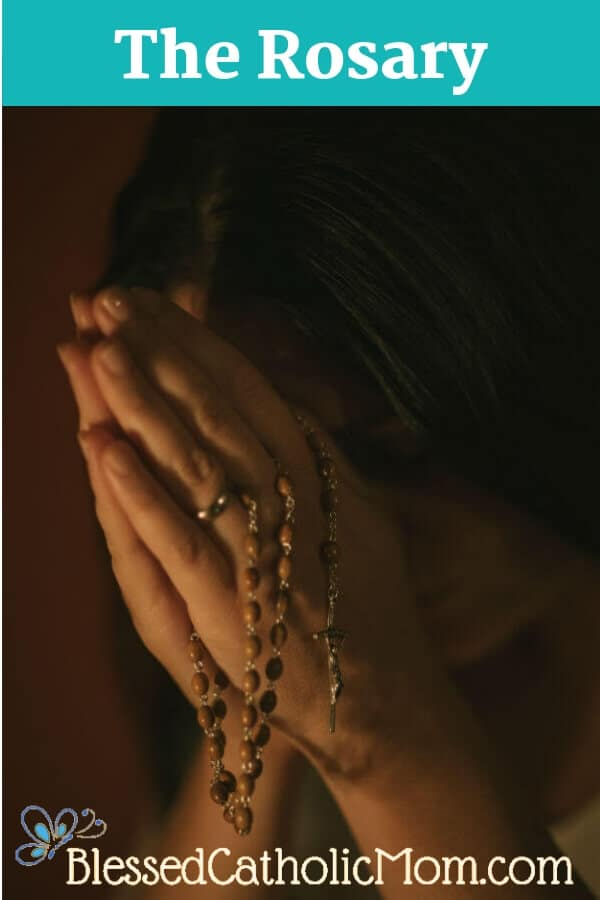 Image of a woman's hands clasping the Rosary, her head bent over her hands as she prays.