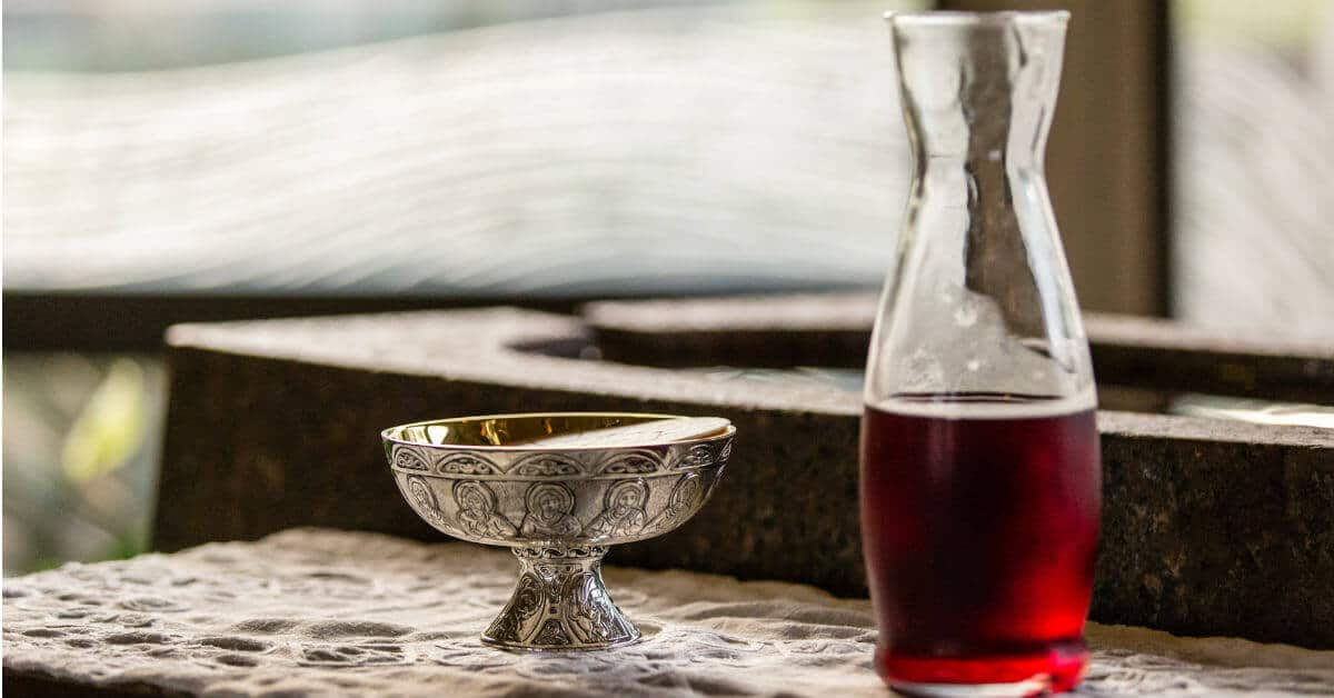 Image of a ciborium of hosts and a carafe of wine on a table at church.