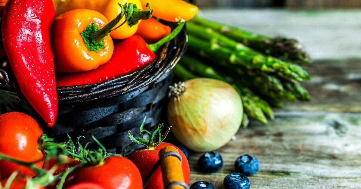 Picture of a basket with red, orange,and yellow skinny peppers. On the wooden table beside the basket is asparagus, an onion, tomatoes, and blueberries.