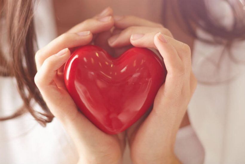 Image of a woman's hands holding a red heart. Title above image: 7 Ways to Take Care of Yourself. Logo on bottom if image: A blue graphic butterfly and the words Blessed Catholic Mom.