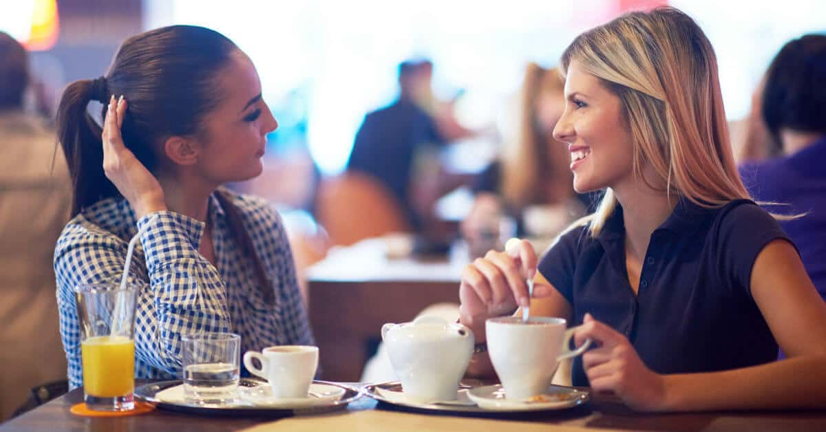 Image of two women sitting facing each other at a table at a restaurant. They each have cups of tea or coffee buy them.