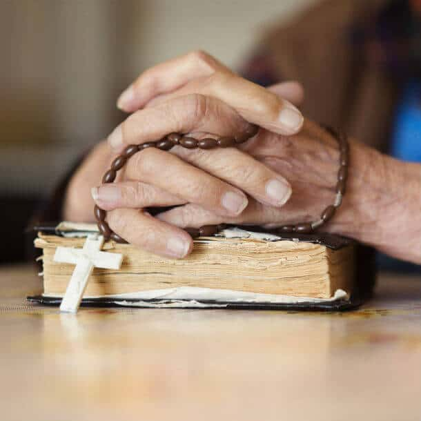 Image of two hands folded together holding a Rosary and resting on top of a Bible.
