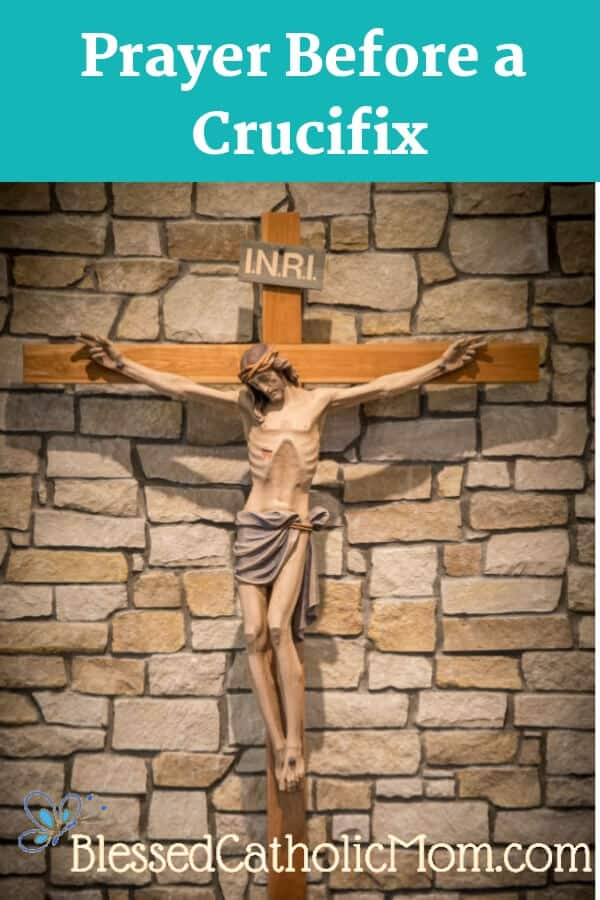 Image of a crucifiz on from of a tan brick wall. Prayer Before a Crucifix is the title at the top of the image; Blessed Catholic Mom is at the bottom of the image.