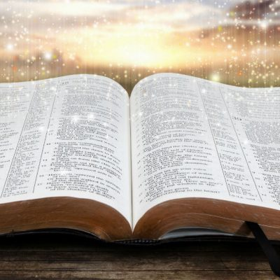 Image of an open Bible on a table with a vibrant sky above it.