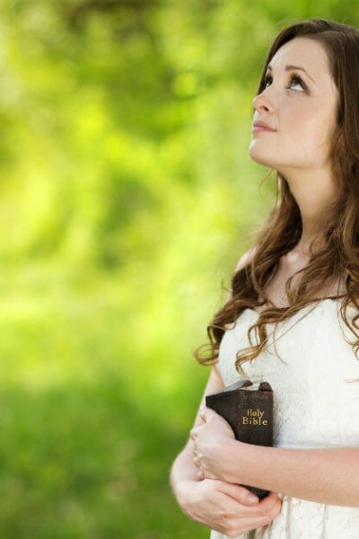 Image of a woman in a white dress holding a Bible, standing outside by trees, and looking up at the sky.