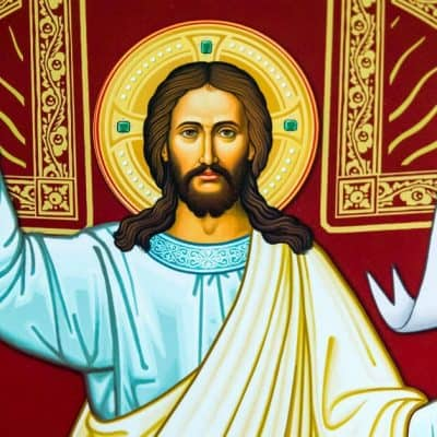 Image of an icon of Jesus holding two fingers up on His right hand and holding a white banner with a golden cross in his left hand.