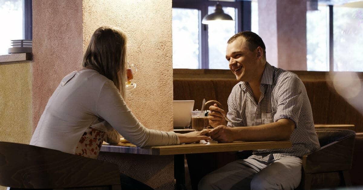 Image of a couple eating a meal together and holding hands at a the table.