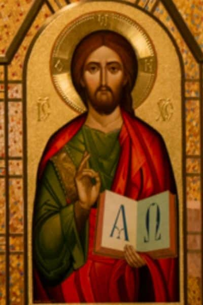 Image of Jesus holding up one finger of one hand and holding a book in the other with the characters for Alpha nd Omega drawn on the two pages that are open and facing the viewer.