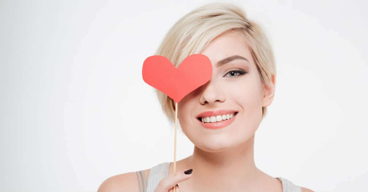 Image of a smiling woman with short blond hair holding a red heart on a stick in front of her right eye.