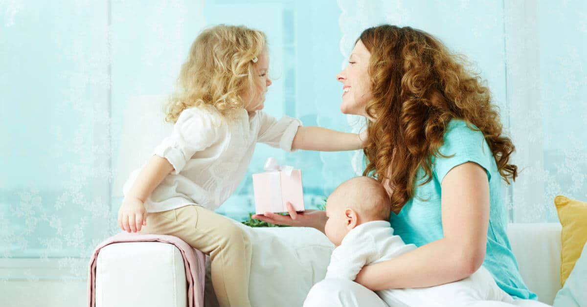 Image of a smiling Mom sitting with young daughter and holding a baby on her lap.