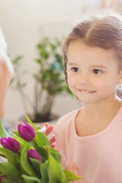 Image of a little girl giving purple tulips to her mother.
