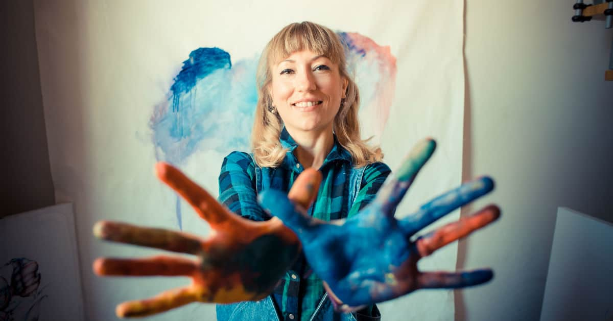 Image of a woman painter in her studio smiling at the camera and holding out her painted hand, palms out.