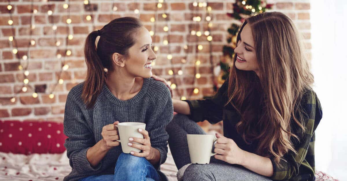 Image of two women sitting, holding coffee mugs and talking. It looks like one is comforting the other with her arm on her friend's back.