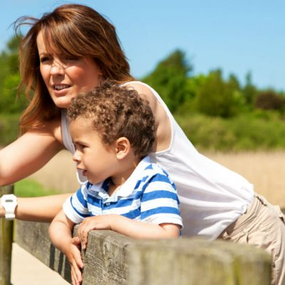 Image of a young mom and her young son leaning on a wooden d=fence outside. She is pointing and explaining something to her little son.