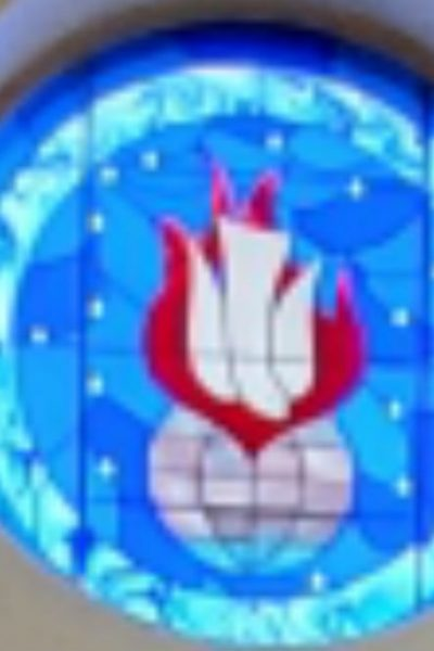 Image of a stained glass window of the Holy Spirit: a white dive pointing down towards the world with a red flame behind it.