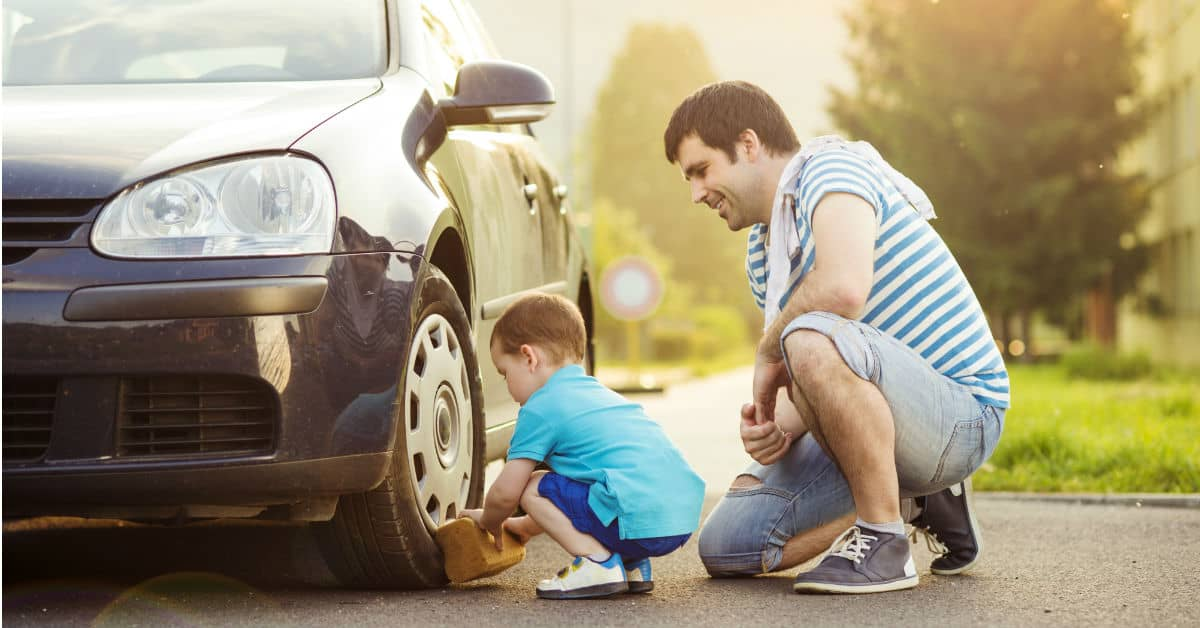 Image of a little boy washing the tire of a car while his father looks on smiling.