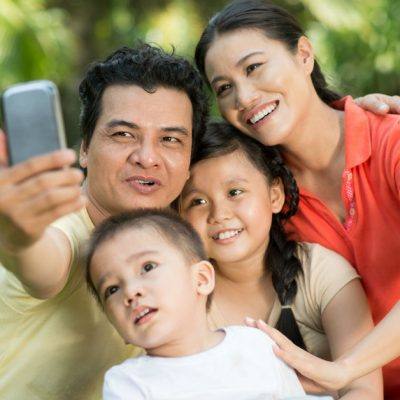 Image of a family sitting on the grass with the father taking a photograph of everyone.