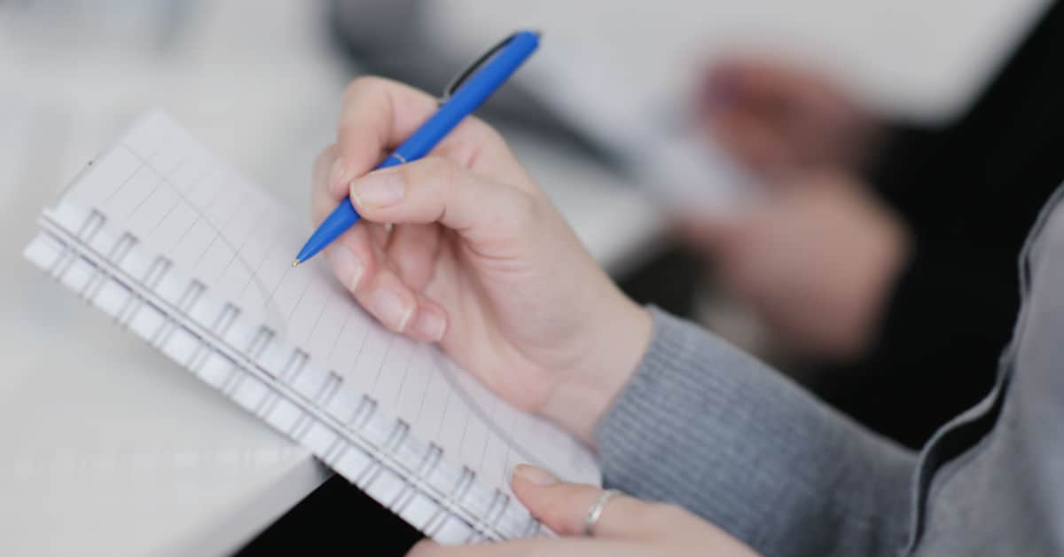 Image of a hand holding a blue pen hovering above a spiral notebook.