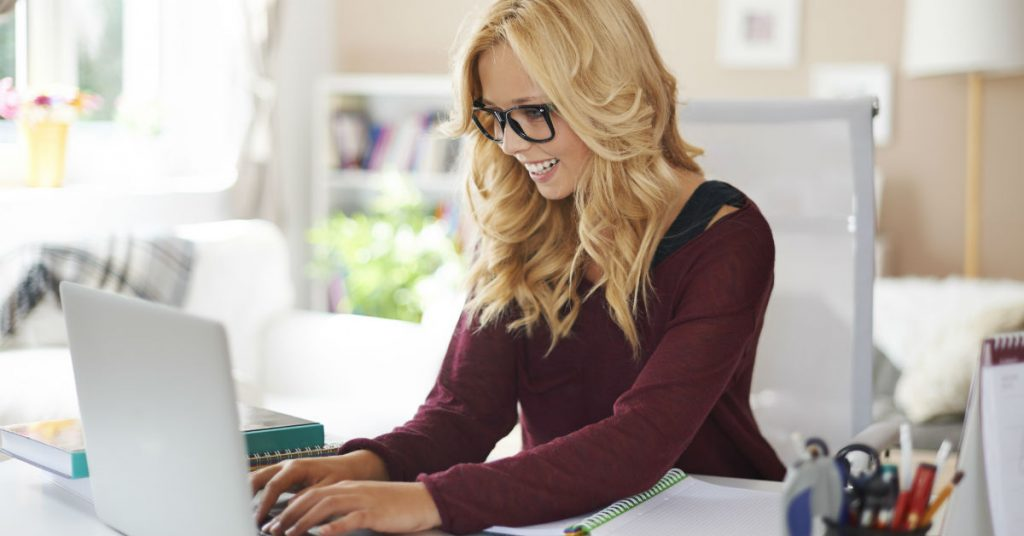 Image of a smiling blonde woman with glasses using a laptop at home.