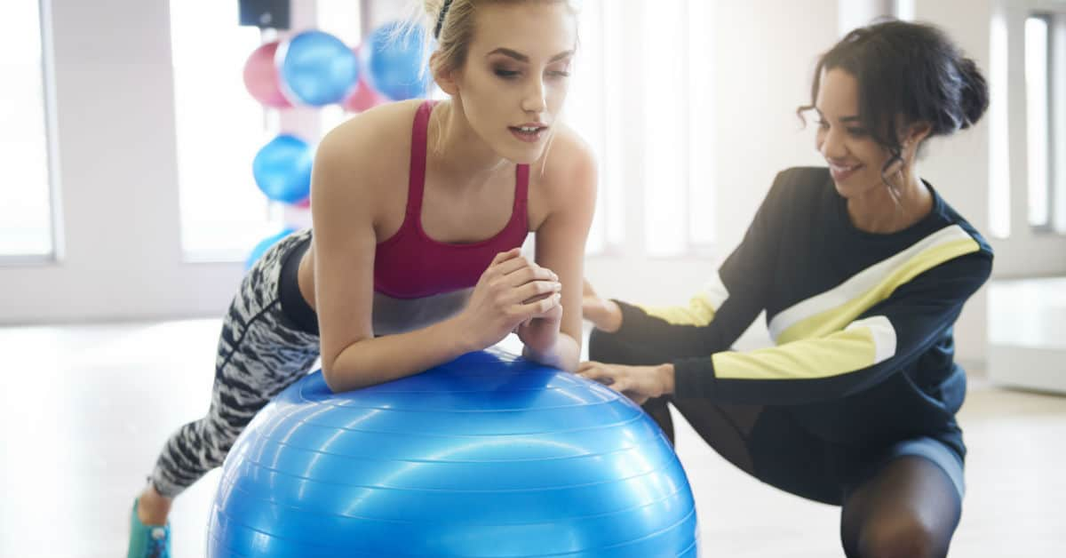 Image of a woman leaning on an exercise bell with a woman couched down beside her to coach her.