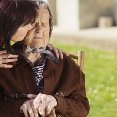 Image of a young woman leaning over to kiss on the cheek an older woman who is sitting down on a chair outside while she is holding a cane and has her eyes closed.