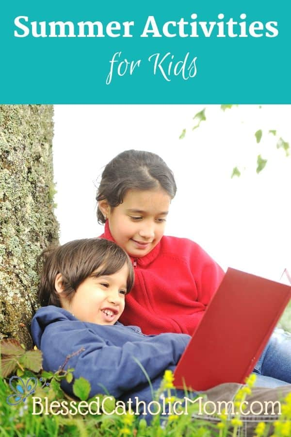 Image of a boy and a girl sitting under a tree outside looking at a book.