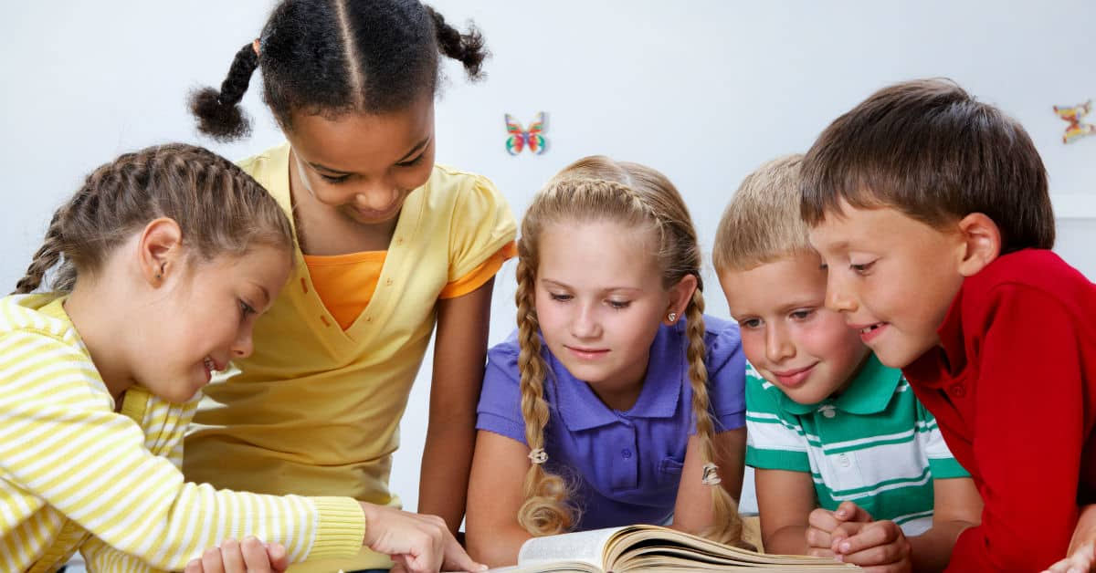 Image of children gathered around a table looking at an open book on the table.