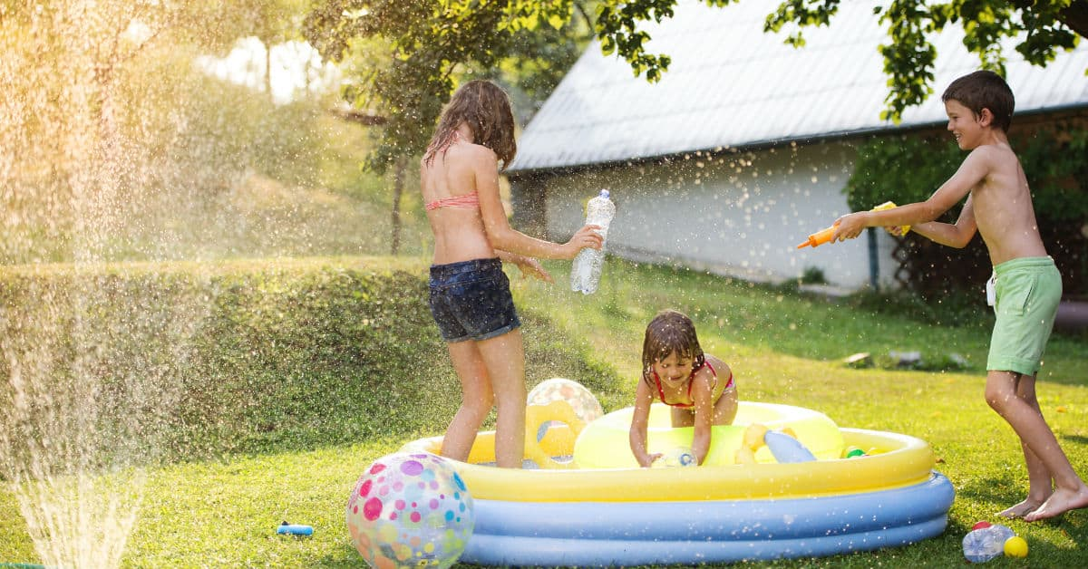 Three kids playing wiht the sprinklers, squirt guns, and an inflatable pool on a lawn in summer.