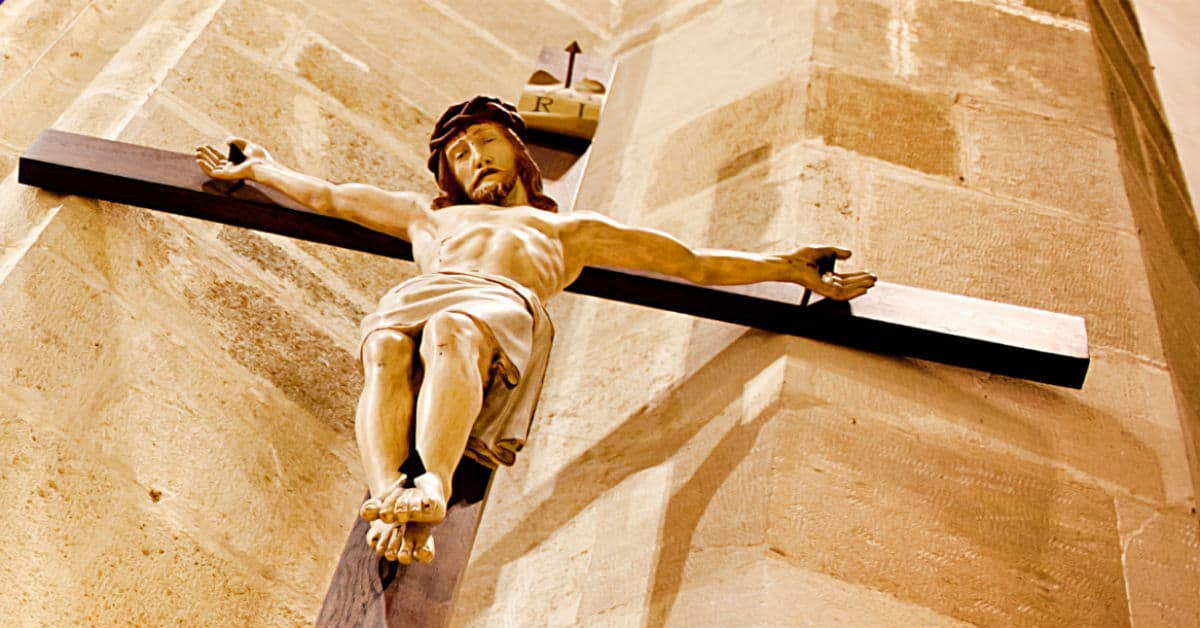 Image of a great wooden cross with Jesus Christ crucified hanging high in a church.