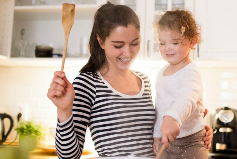 Image of a mom holding her daughter as the daughter is stirring food in a pot on the stove.