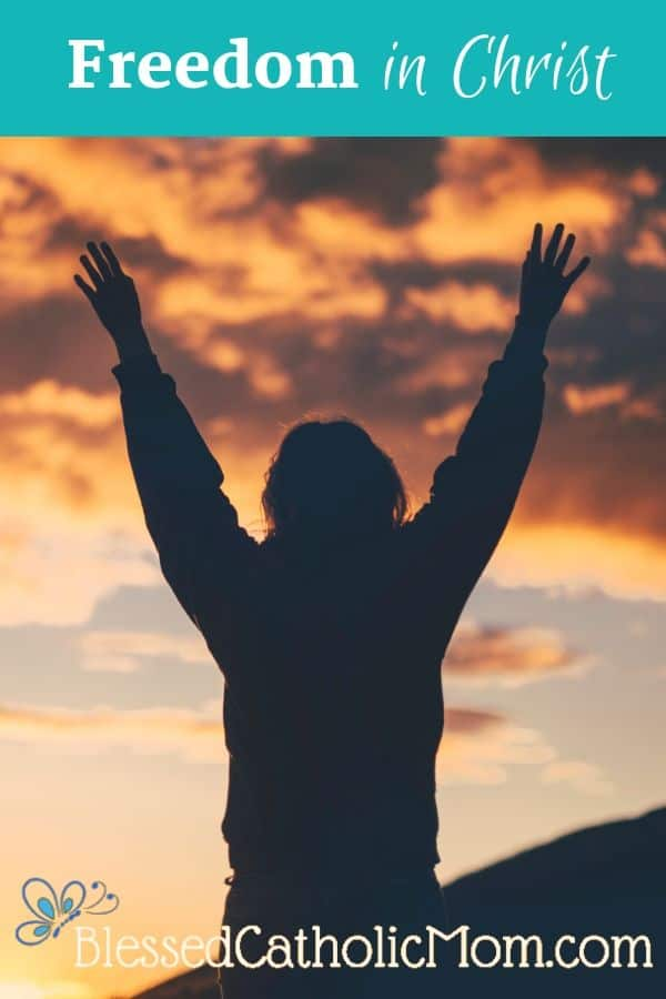 Image of a person standing with hands open and arms raised, facing a sunset.