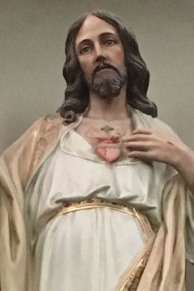 Image of a statue of Jesus with one hand on His Sacred Heart and the other held out as if in blessing to us.
