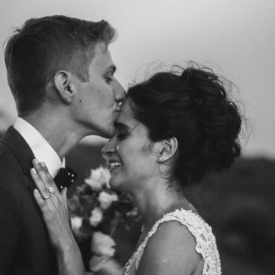 Image of a young just married couple standing together and the husband is kissing his wife's forehead. Photo from Cathopic.