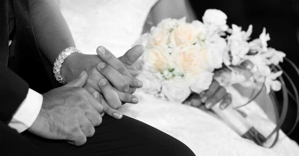 Image of a bride and groom's hands clasped together beside the bridal bouquet. Photo from Cathopic.