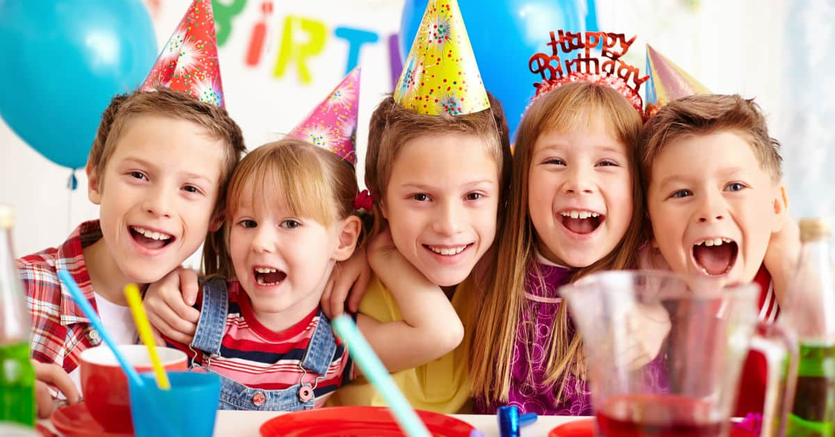 Image of five kids at a birthday party gathered together behind a table with food all smiling at the camera.