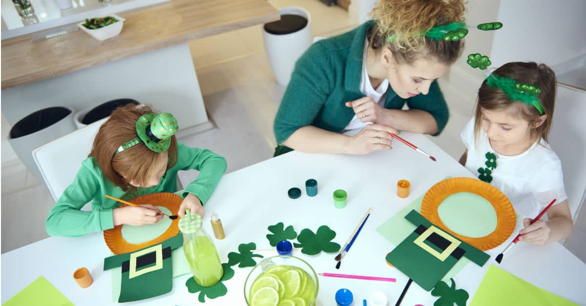 Image of a woman and two children making St. Patrick's Day crafts.