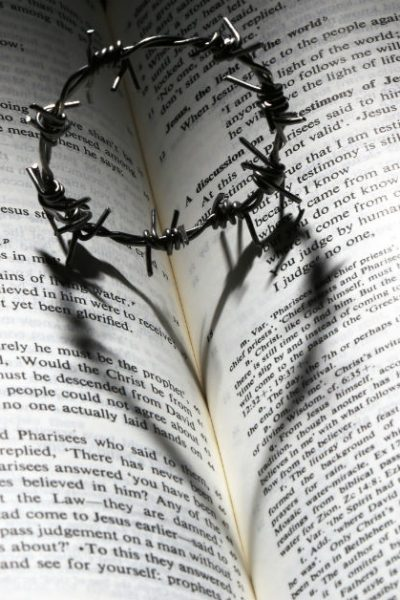 Image of a small metal crown of thorns on top of an open Bible. The shadow of the crown on the Bible is in the shape of a heart.