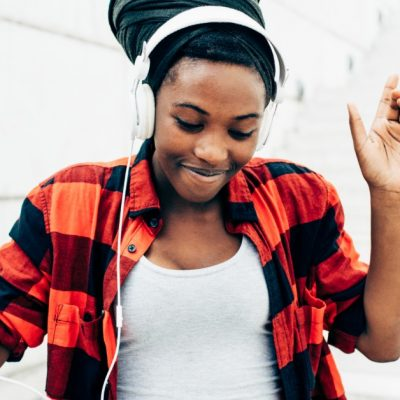 Image of a smiling woman listening to music while wearing headphones.