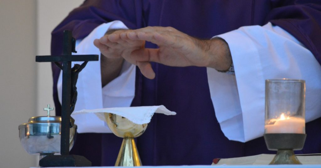 Image of a priest's hands over a covered chalice on the altar. A crucifix is also on the altar.