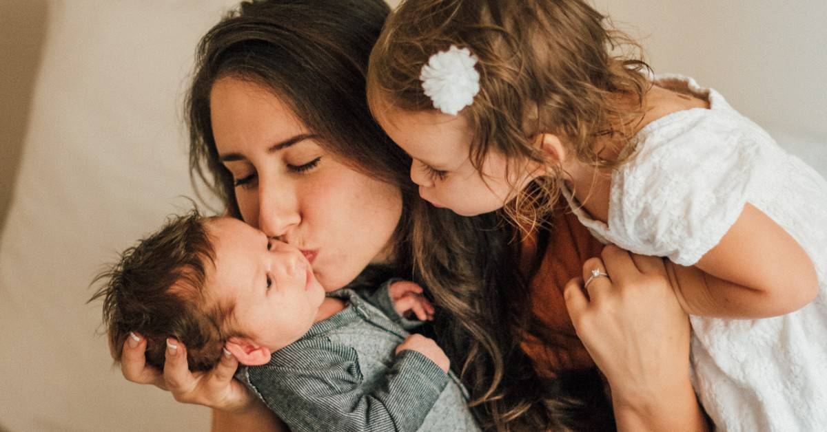 Image of a mom holding a baby while his little sister leans over their mom's shoulder to get a closer look at him.