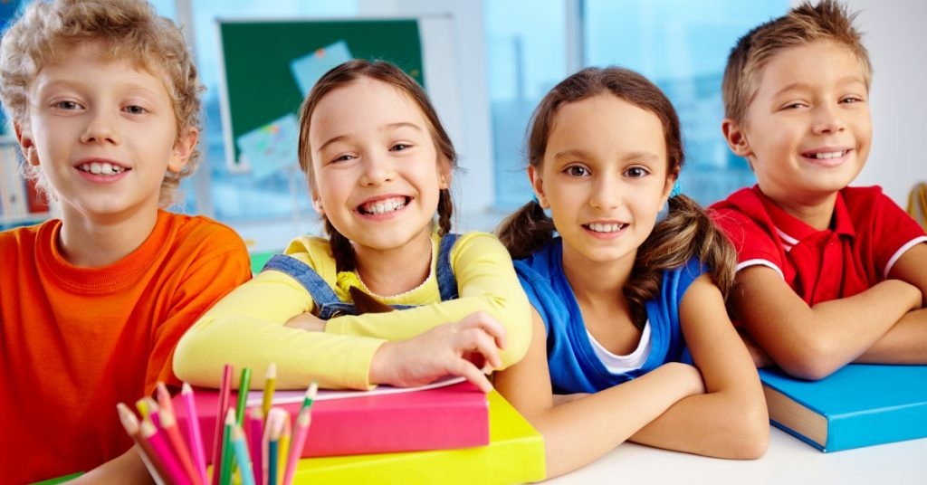 Image of four kids (two boys and two girls) sitting at a table with books and colored pencils smiling at the camera.