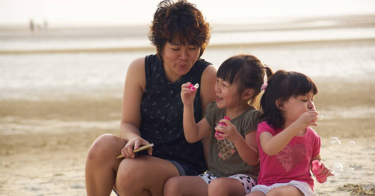 Image of a mom with two daughters at the beach making soap bubbles together.