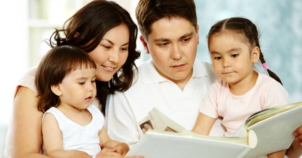 Image of a family-Dad, Mom, son, and daughter-reading a book together.