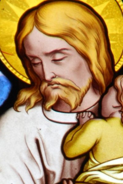 Image of a stained glass window of Jesus holding a little child in His arms.