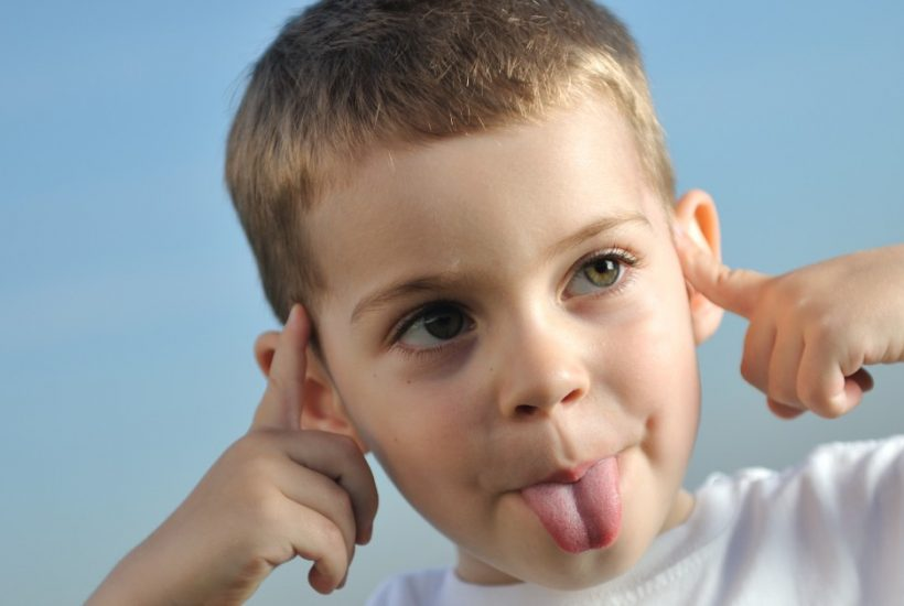 Image of a boy sticking out his tongue and putting his fingers in his ears so he will not need to listen to a parent.